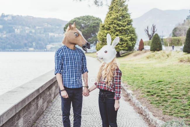 Couple wearing horse and rabbit masks holding hands, Lake Como, Italy — Stock Photo