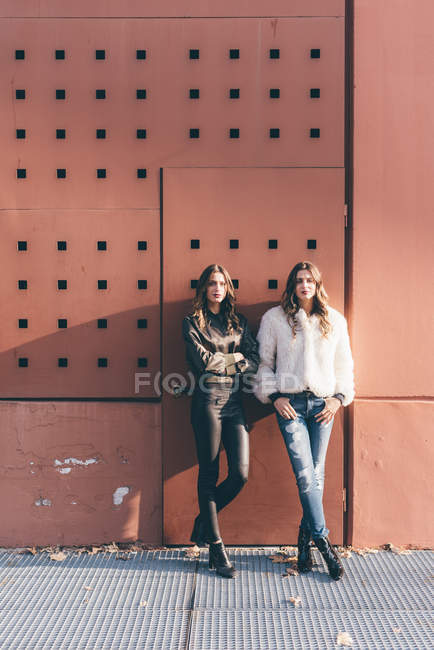 Ritratto di gemelle, all'aperto, appoggiata al muro — Foto stock