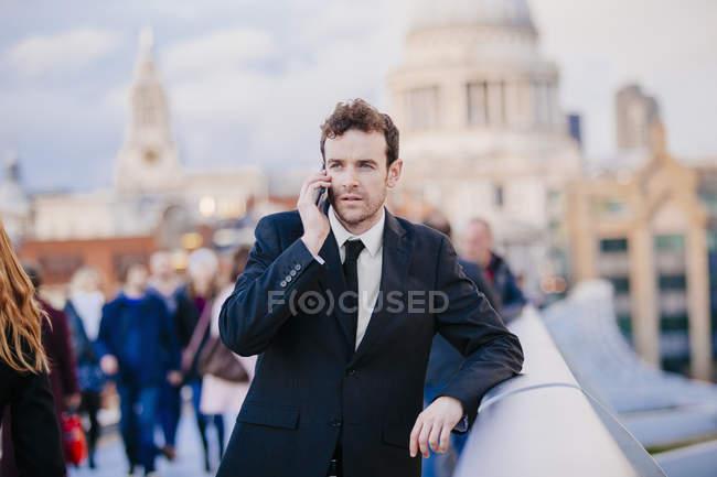 Homme d'affaires bavardant sur smartphone tout en s'appuyant sur Millennium bridge, Londres, Royaume-Uni — Photo de stock