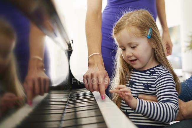Pais ensinando filha a tocar piano — Fotografia de Stock