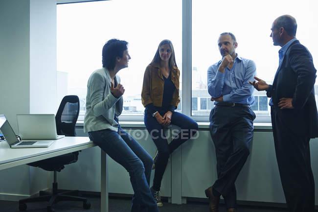Empresários masculinos e femininos conversando no escritório — Fotografia de Stock