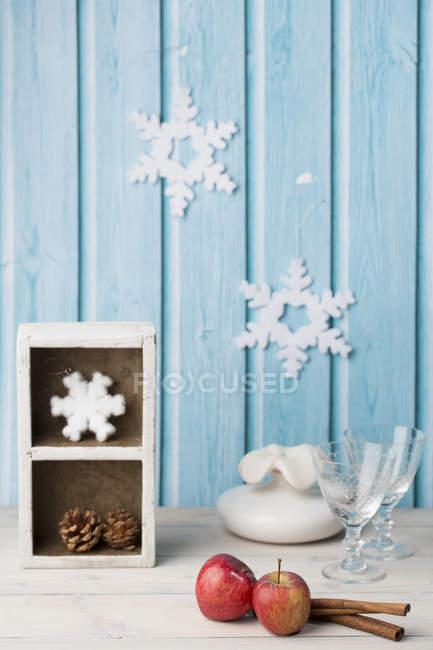 Красные яблоки, корицу, бокалы, шишка, бумажные снежинки на голубой стене — стоковое фото
