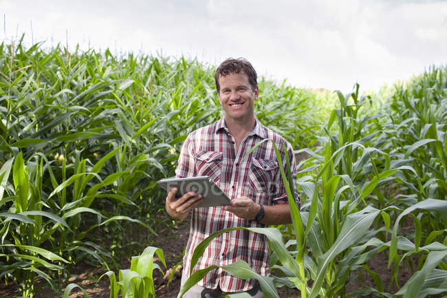 Landwirt steht mit digitalem Tablet auf Feld — Stockfoto