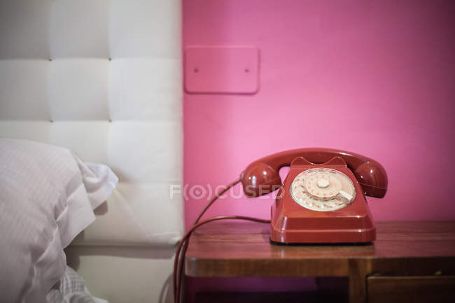 Red rotary telephone on bedside table — Stock Photo