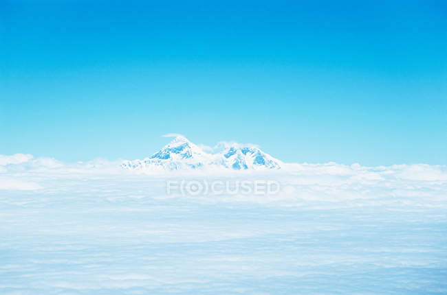 Snowcapped mountain peak surrounded by clouds — Stock Photo