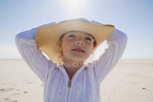 Mädchen mit Strohhut posiert am Strand — Stockfoto