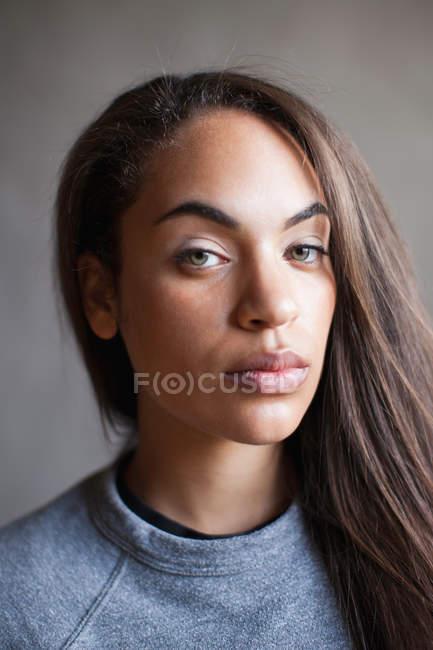 Портрет молодой женщины в студии, смотрящей в камеру — стоковое фото