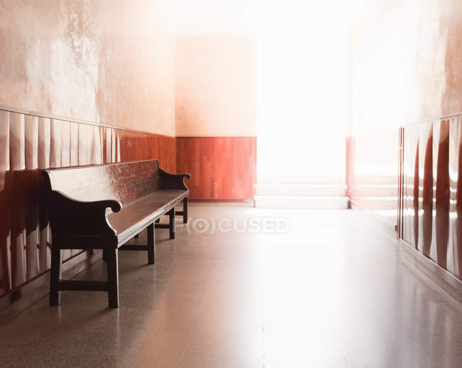 Empty bench in illuminated corridor interior — Stock Photo