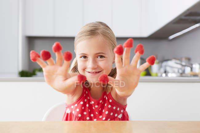 Girl putting raspberries on fingers — Stock Photo