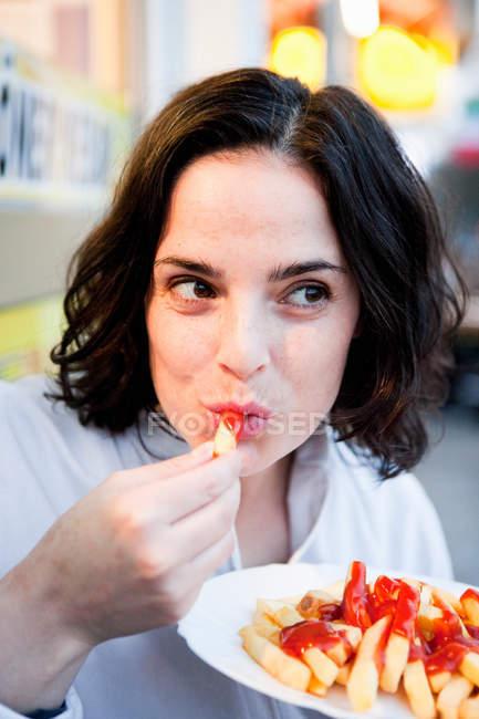 Женщина ест картошку фри с кетчупом и смотрит в сторону — стоковое фото