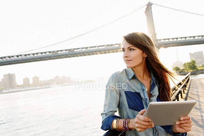Jeune femme avec tablette numérique, Manhattan Bridge, Brooklyn, USA — Photo de stock