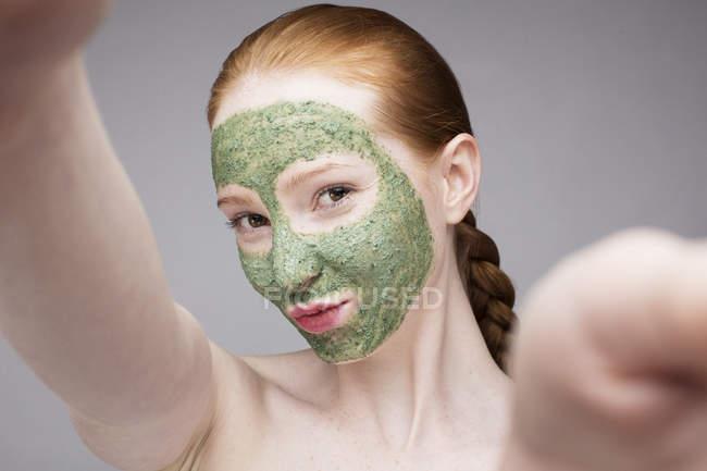 Junge Frau mit Gesichtsmaske, schmollend vor der Kamera — Stockfoto