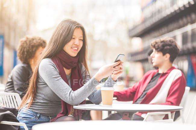 Frau sitzt im Bürgersteig-Café und schaut lächelnd aufs Smartphone — Stockfoto