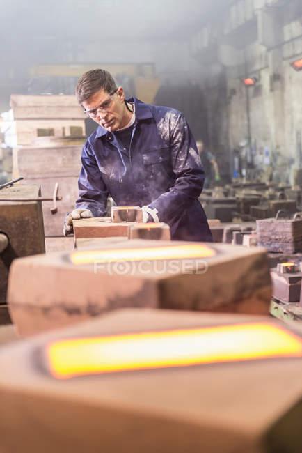 Travailleur inspectant le métal fondu chaud dans les moules de fonderie — Photo de stock