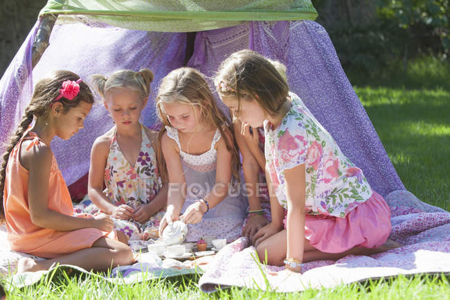 Five girls playing with toy tea set in garden — Stock Photo