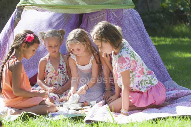 Пять девушек играют с игрушечным чайным сервизом в саду — стоковое фото