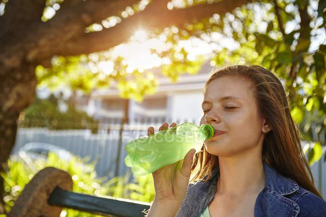 Дівчинка-підліток, сидячи на лавці, пити м'який напій з пляшки — стокове фото