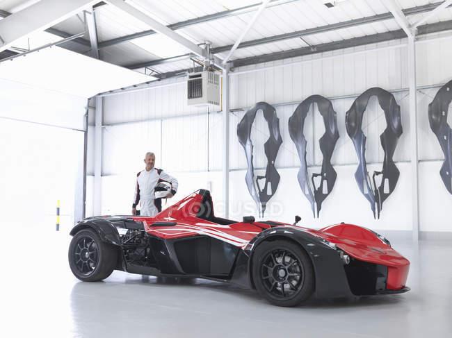 Rennfahrer mit Supersportwagen in der Fabrik mit Carbon Fibre Auto Karosserien an Wand — Stockfoto