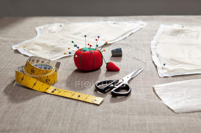 Sewing pattern, pin cushion and tape on table — Stock Photo