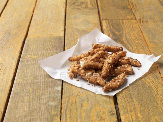 Comida, pescado, varitas super sembrados Solla ligeramente espolvoreado, pintado de amarillo mesa de madera - foto de stock