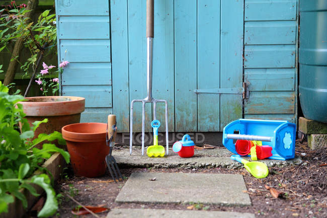Gardening tools, pots and toys outside shed — Stock Photo