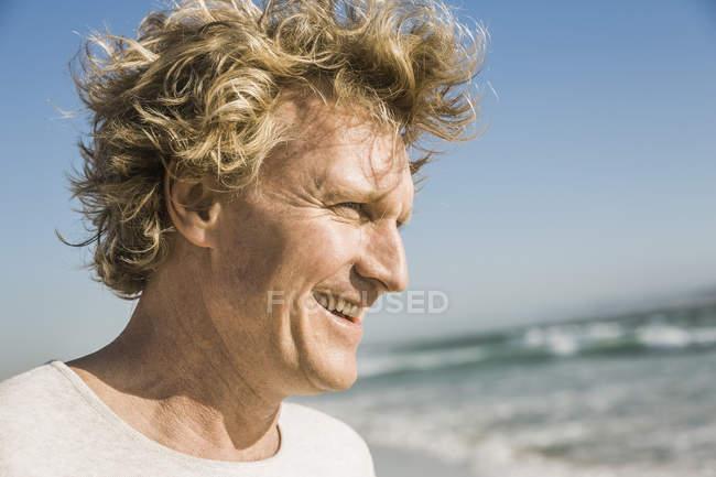 Retrato del hombre por el océano mirando hacia otro lado sonriendo - foto de stock