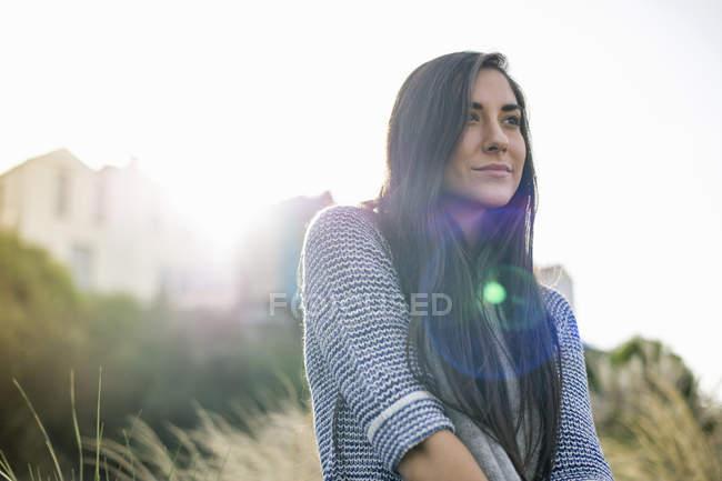 Mujer joven con cabello castaño largo a la luz del sol - foto de stock