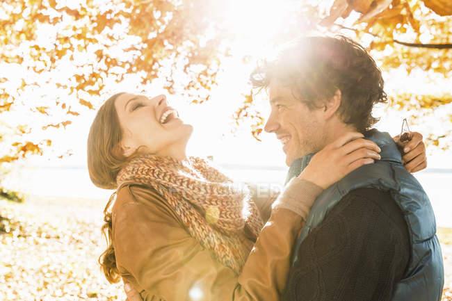 Couple embrasser par l'arbre dans la lumière du soleil — Photo de stock