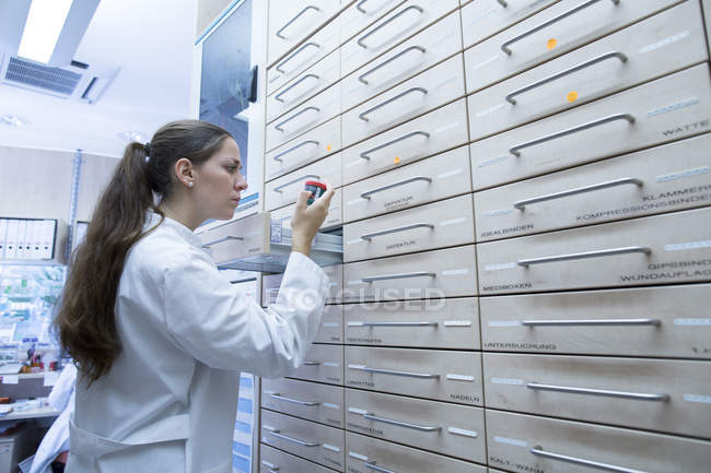 Фармацевт в аптеці відкриття медицина файл ящик — стокове фото