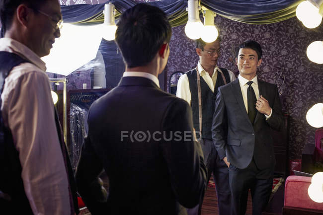 Tailor with young male client trying on new suit in shop — Stock Photo