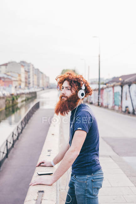 Young male hipster with red hair and beard listening to headphones on city bridge — Stock Photo