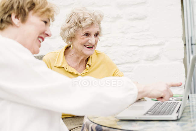 Старша жінка і зріла дочка вказуючи і дивлячись на ноутбук — стокове фото