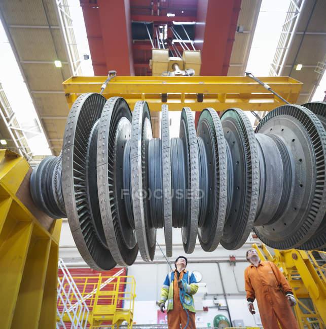 Bankkaufmann und Kranführer heben Turbine während eines Kraftwerksausfalls an, Blick in den niedrigen Winkel — Stockfoto
