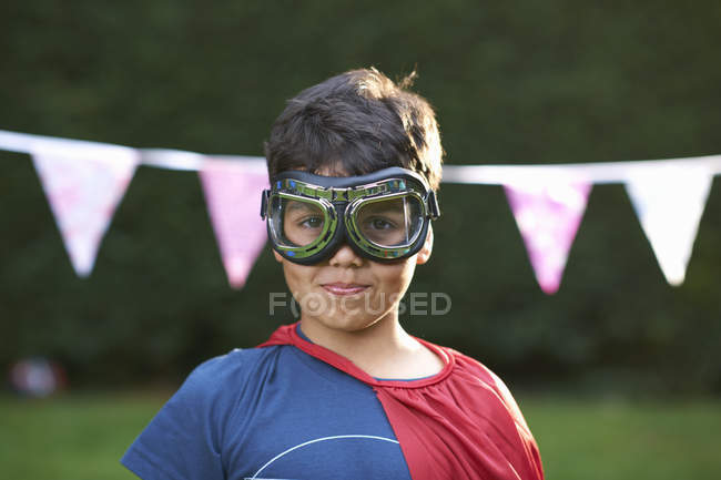 Portrait of boy wearing goggles and cape, looking at camera — Stock Photo