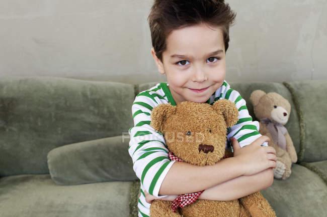 Портрет хлопця на дивані, обіймати плюшевого — стокове фото