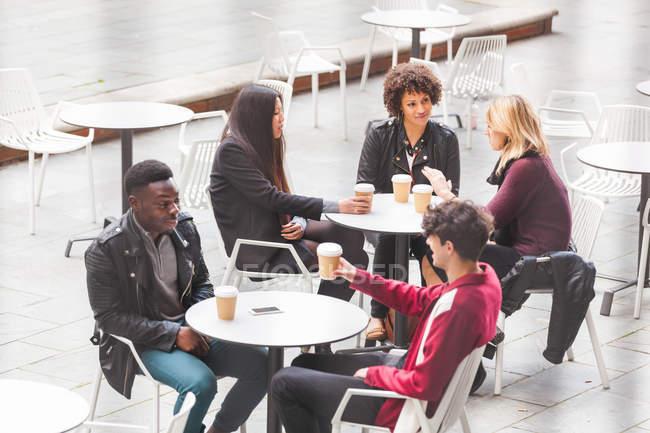 Друзья, сидящие за столиками в кафе на тротуаре и пьющие кофе — стоковое фото