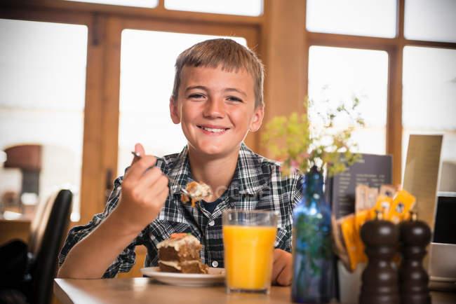 Retrato de menino comendo bolo no café da fazenda — Fotografia de Stock