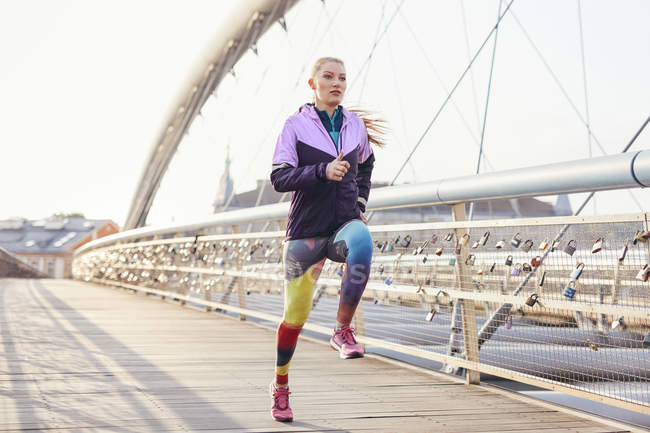 Mid adult female runner running at speed on city footbridge — Stock Photo