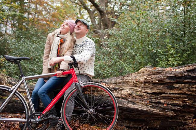 Casal sentado no log com bicicleta — Fotografia de Stock