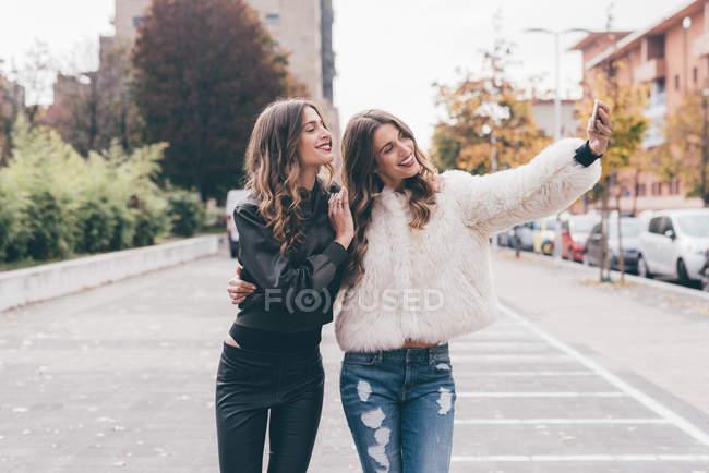 Sorelle gemelle, camminare all'aperto, scattare selfie utilizzando lo smartphone — Foto stock