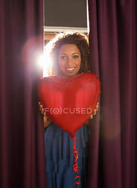 Mulher segurando balões em forma de coração — Fotografia de Stock