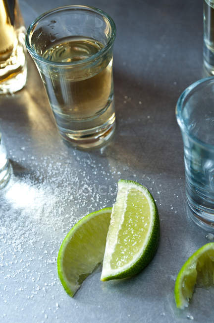 Tequila shots with lime slices and salt on table — Stock Photo