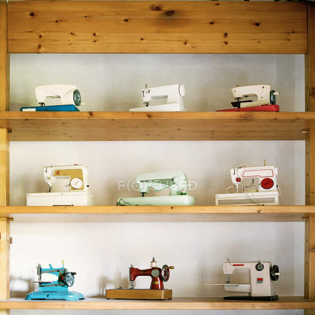 Vintage sewing machines collection on shelves — Stock Photo