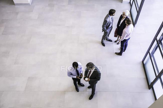 Vista ad alto angolo di uomini d'affari e uomini d'affari che discutono nell'atrio dell'ufficio — Foto stock