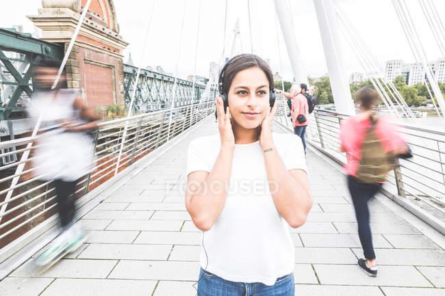 Junge Frau steht auf Brücke und trägt Kopfhörer — Stockfoto