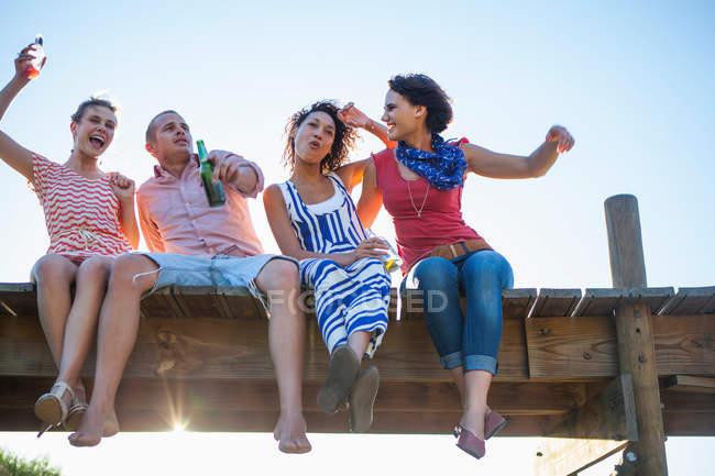 Giovani amici seduti insieme sul molo, vista angolo basso — Foto stock