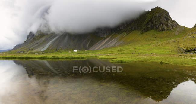 Nubes bajas sobre las montañas que se reflejan en el agua del lago - foto de stock
