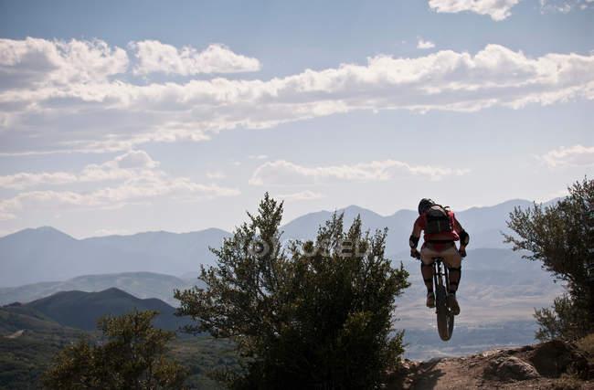 Вид сзади на горного велосипедиста на скалистой тропе — стоковое фото