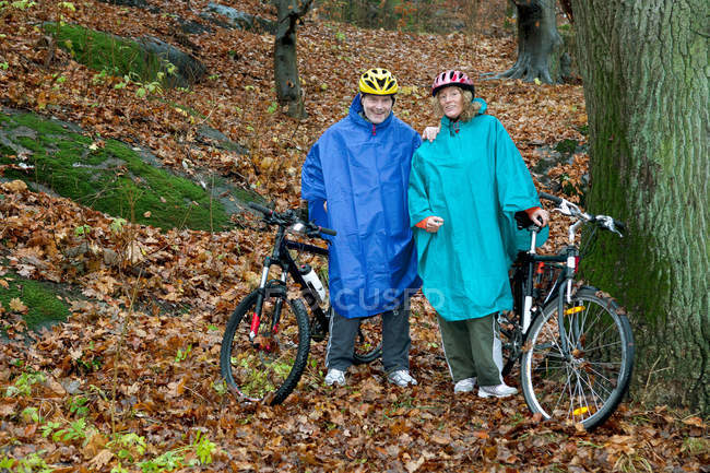 Portrait of mature couple on cycle ride in forest — Stock Photo