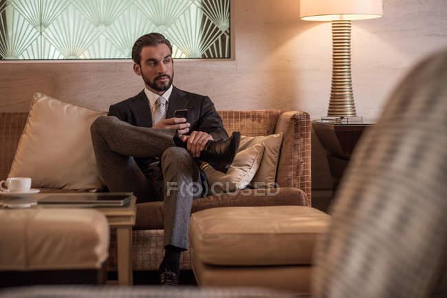 Jungunternehmer sitzt mit Smartphone auf Hotellobby-Sofa — Stockfoto